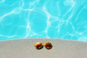 Sunglasses beside swimming pool