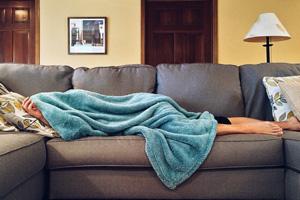 Woman-under-blanket-on-sofa