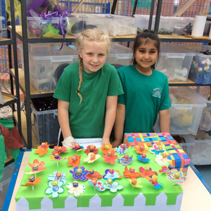 Two girls taking part in the Fiver Challenge selling products on a stall