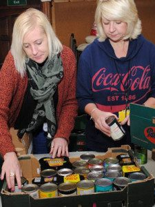 Jennifer and Julie sorting tins at Merthyr Cynon Food Bank for Wales Action Week