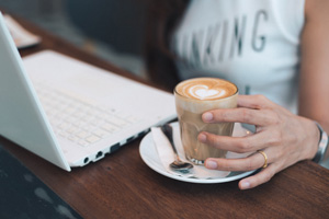 Woman-drinking-coffee-sat-at-laptop