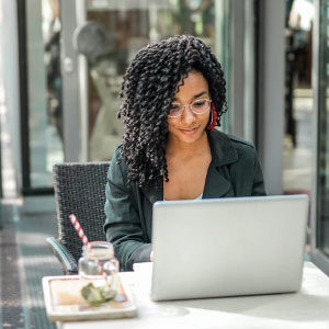 Woman-working-on-laptop-outside-cafe